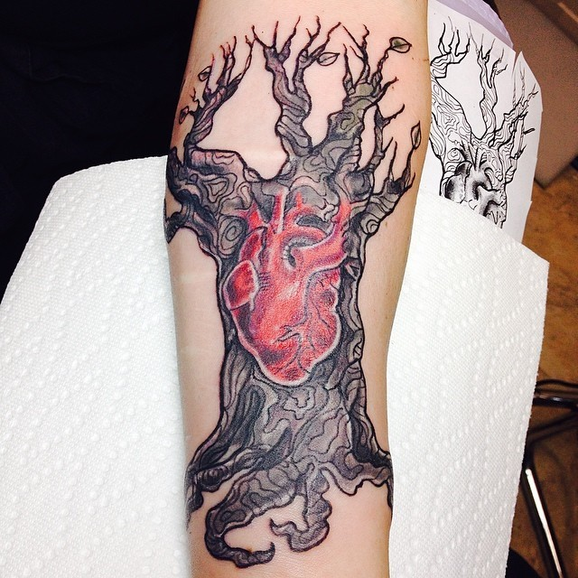 Carelessly painted colored big tree tattoo on forearm stylized with red human heart