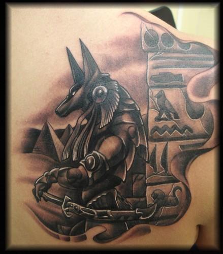 Cartoon like black and white antic Seth God tattoo on back