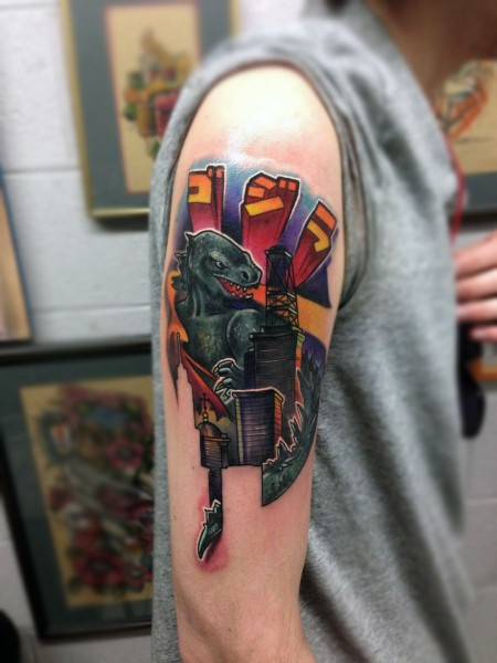 Cartoon like colored big Godzilla shoulder tattoo with lettering