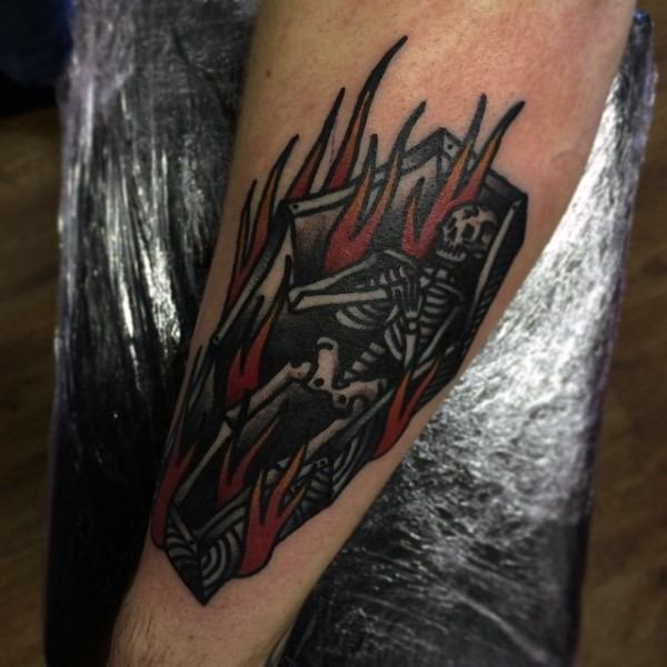 Cartoon like colored burning coffin with skeleton tattoo on arm