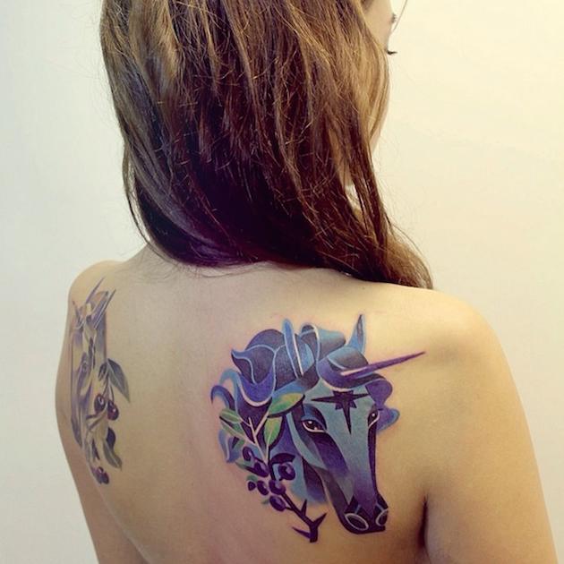 Cartoon like colored funny unicorn tattoo on shoulder