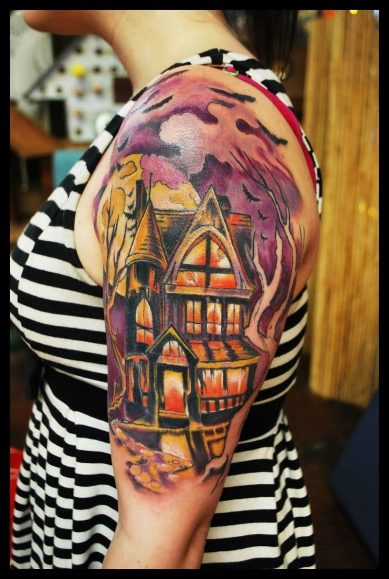 Cartoon like colored shoulder tattoo of old house with bats