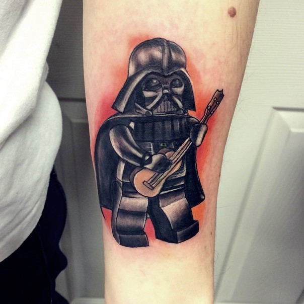 Cartoon like colored tiny arm tattoo of lego Darth Vader with guitar