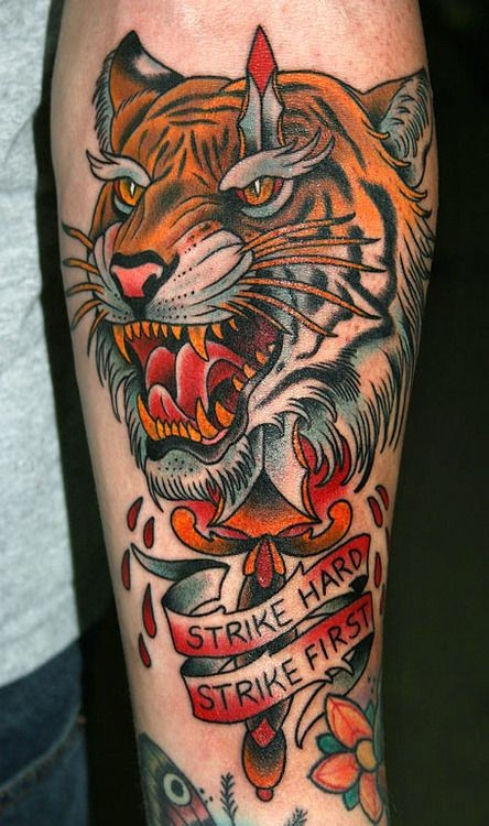 Cartoon like designed and colored tiger head with bloody sword tattoo on forearm stylized with lettering