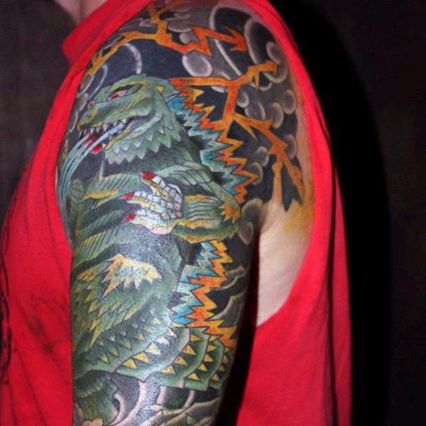 Cartoon like multicolored Godzilla tattoo on arm