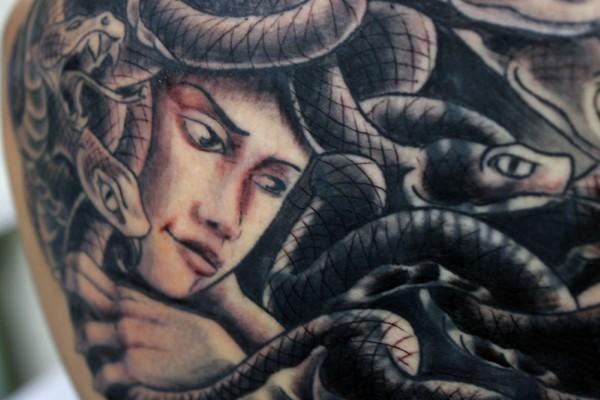 Cartoon like multicolored Medusa head with snakes tattoo on back