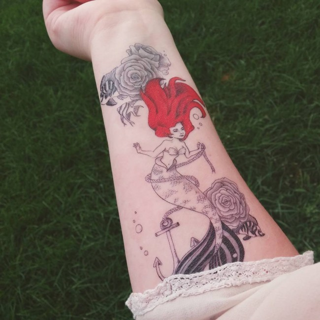 Cartoon like painted red-head mermaid tattoo on forearm with roped anchor and flowers