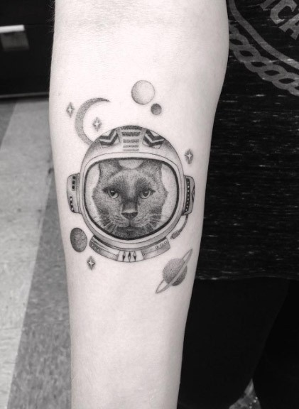 Cartoon style black and white space cat tattoo on forearm stylized with planets