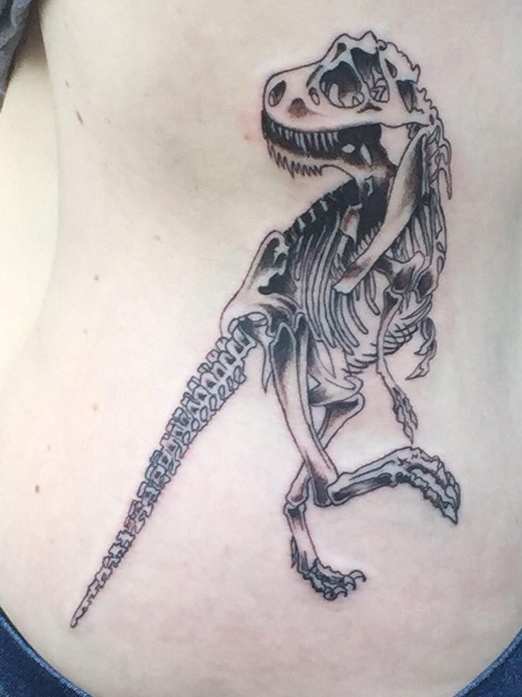 Cartoon style black ink side tattoo of dinosaur skeleton