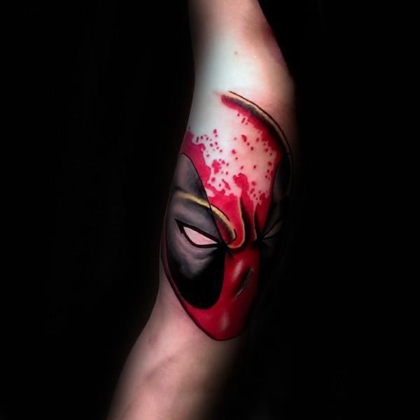 Cartoon style colored arm tattoo of bloody Deadpool head