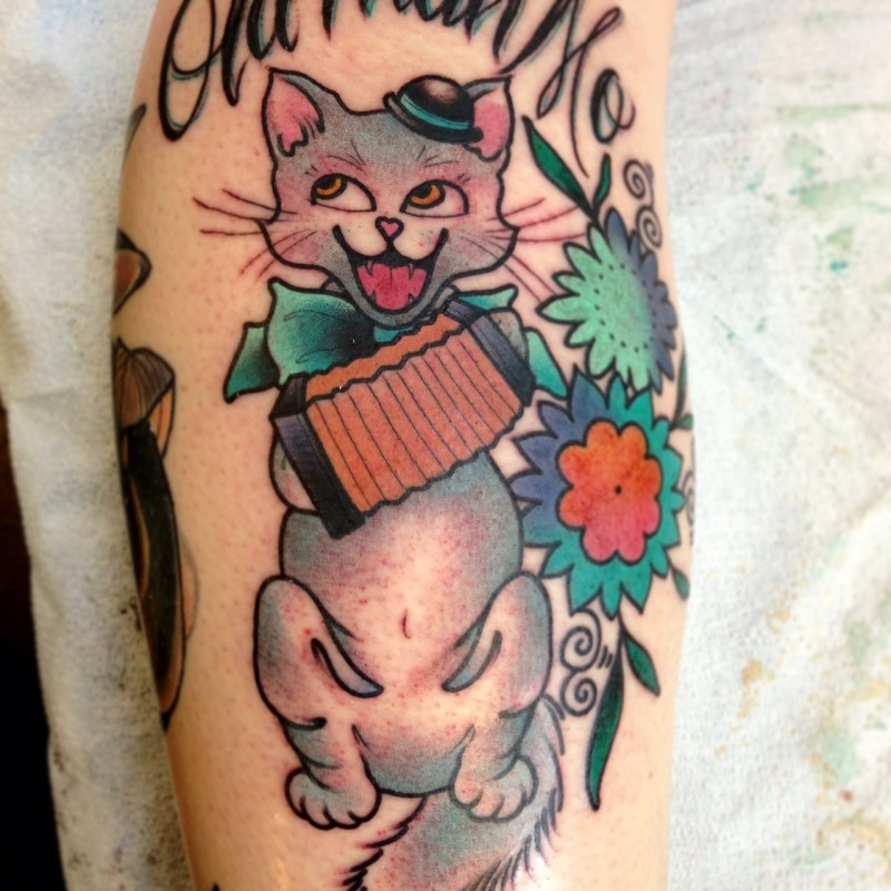 Cartoon style colored arm tattoo of cat with flowers and accordion
