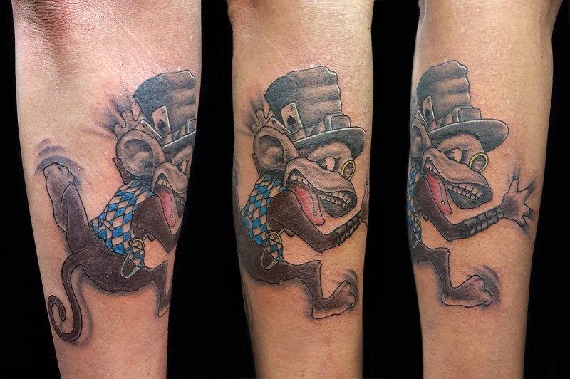 Cartoon style colored arm tattoo of funny monkey with hat