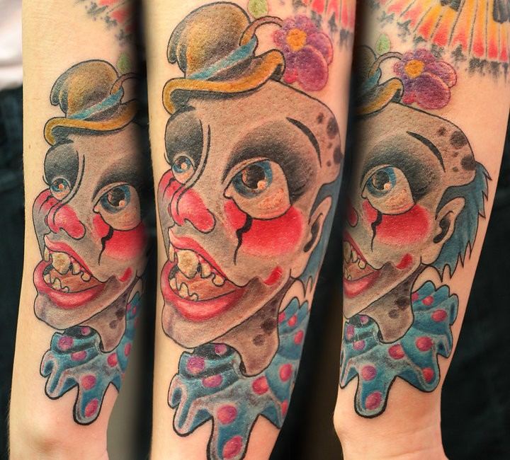 Cartoon style colored arm tattoo of monster clown