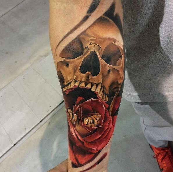 Cartoon style colored arm tattoo of scary human skull and rose
