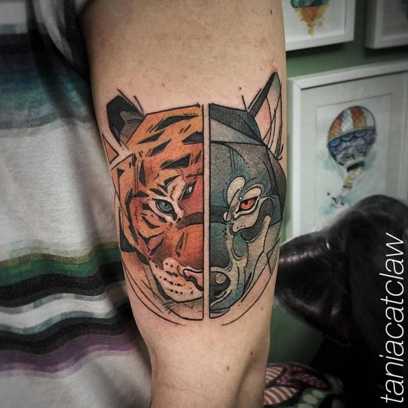 Cartoon style colored biceps tattoo of separated wolf and tiger heads