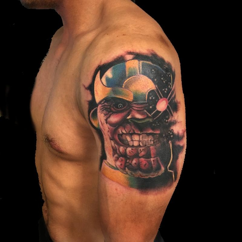 Cartoon style colored evil superhero tattoo on shoulder