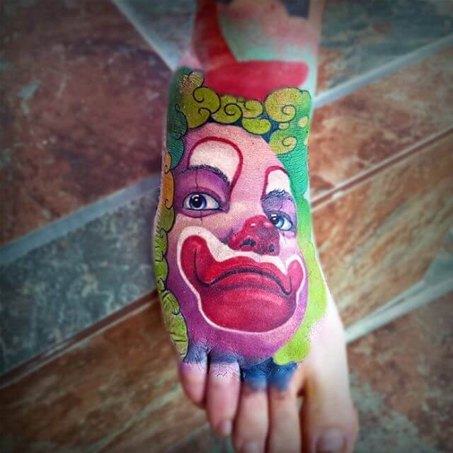 Cartoon style colored foot tattoo of creepy clown face
