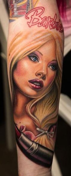 Cartoon style colored forearm tattoo of Barbie doll with lettering