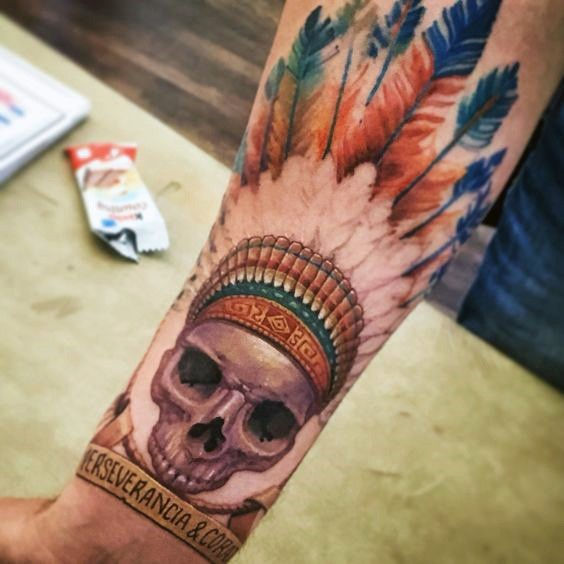 Cartoon style colored forearm tattoo of ancient Indian skull with feather and lettering
