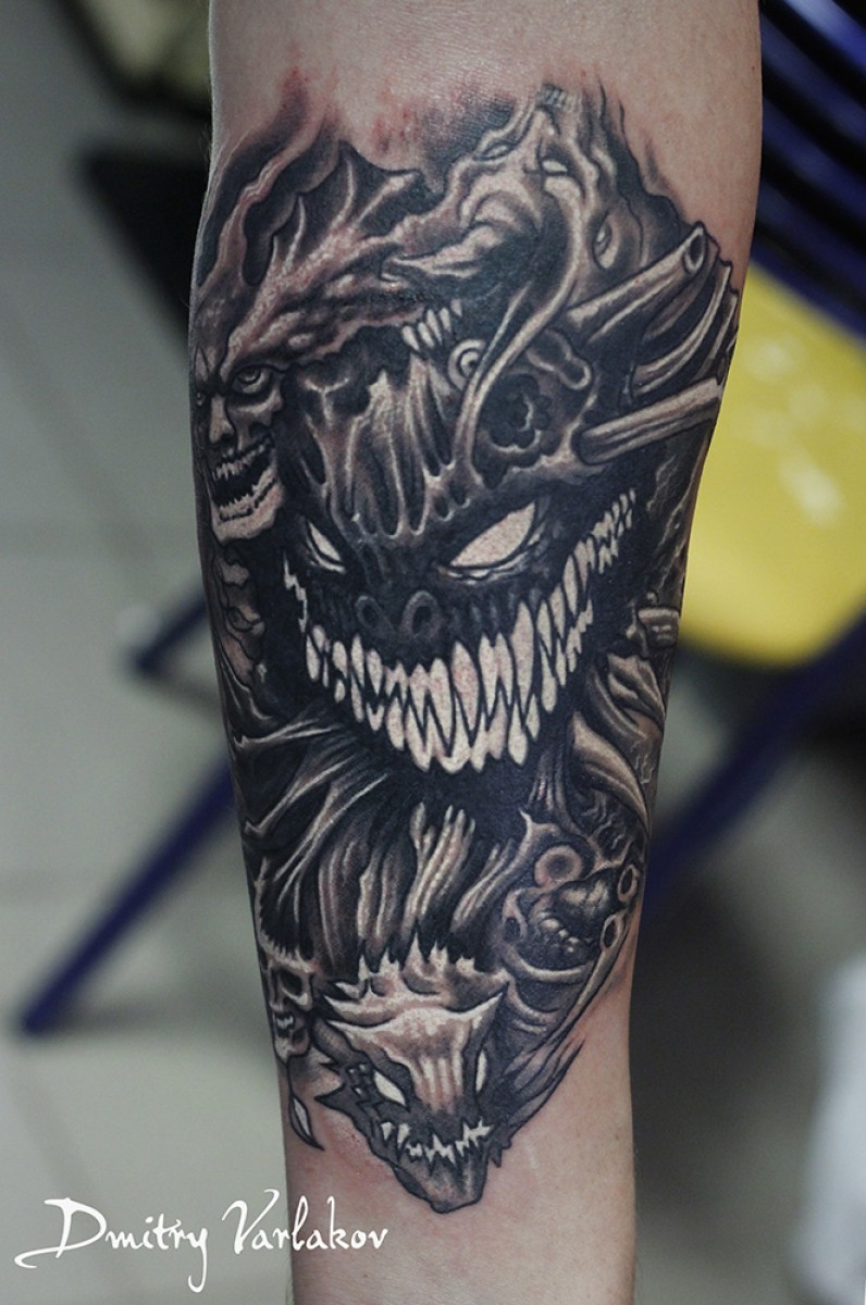 Cartoon style colored forearm tattoo of evil monsters faces
