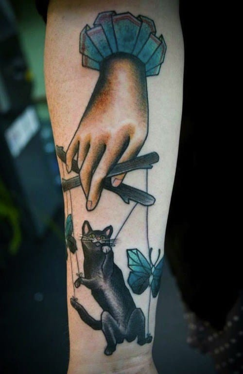 Cartoon style colored forearm tattoo of human hand with cat puppet and butterflies