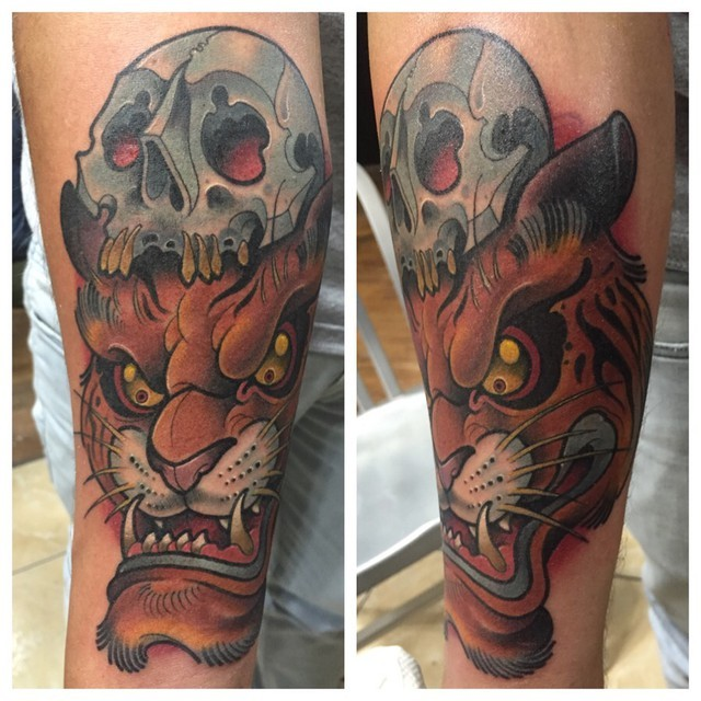 Cartoon style colored forearm tattoo of tiger head with human skull