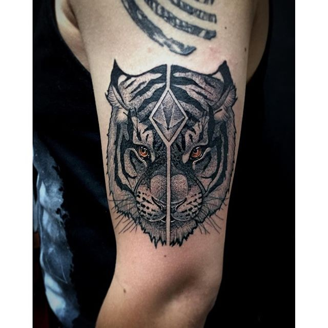 Cartoon style colored shoulder tattoo of tiger head