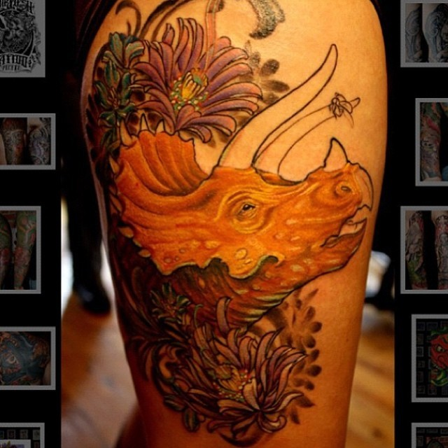 Cartoon style colored thigh tattoo of dinosaur head with flowers