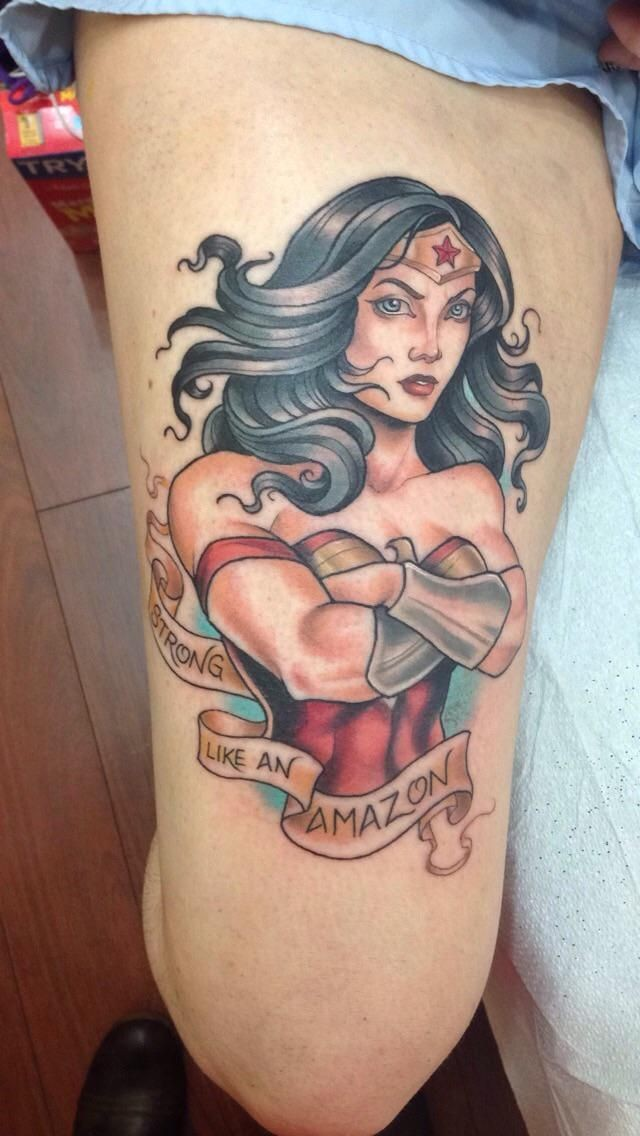 Cartoon style colored thigh tattoo of fantasy Wounder woman and lettering