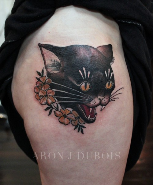 Cartoon style colored thigh tattoo of cat head with flowers
