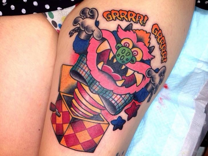 Cartoon style colored thigh tattoo of funny scary toy with lettering