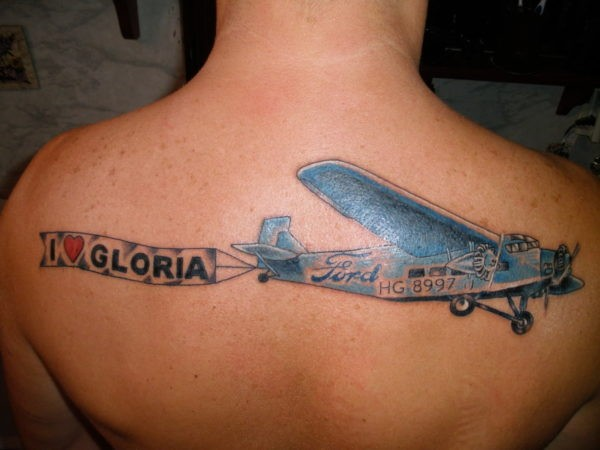 Cartoon style colored upper back tattoo of plane with lettering