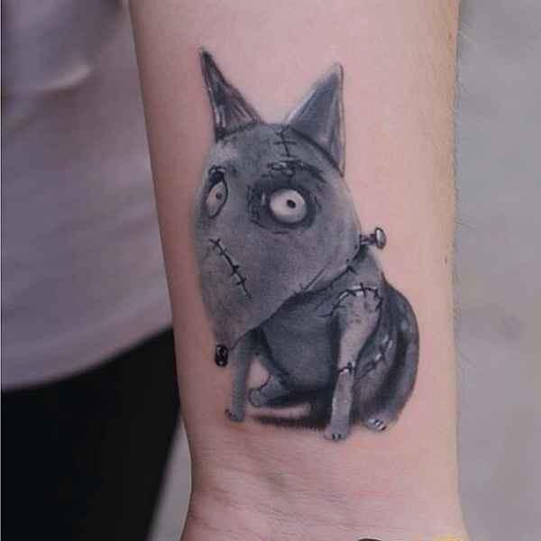 Cartoon style colored wrist tattoo of creepy dog