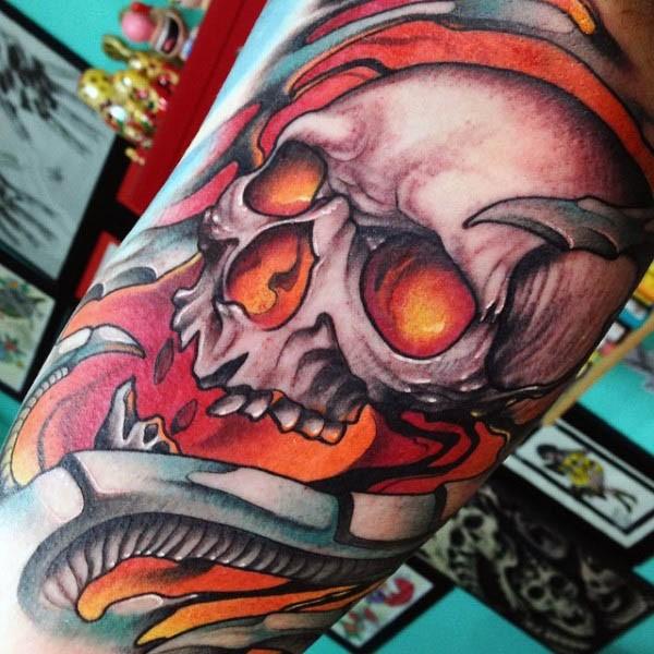Cartoon style colorful demonic skull tattoo on arm stylized with bones
