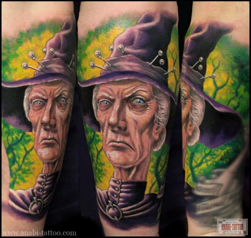 Cartoon style colorful forearm tattoo of evil witch portrait