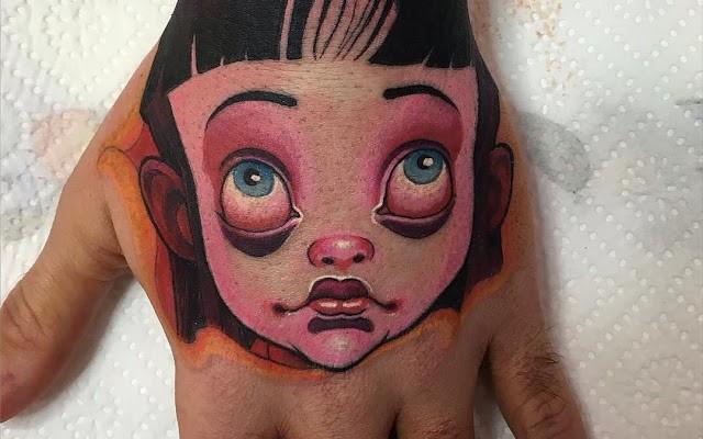 Cartoon style doll portrait tattoo on hand