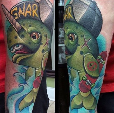 Cartoon style funny looking fish tattoo on forearm stylized with lettering
