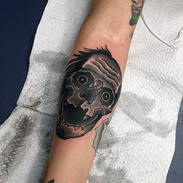 Cartoon style funny looking forearm tattoo of monster skull with blue eyes