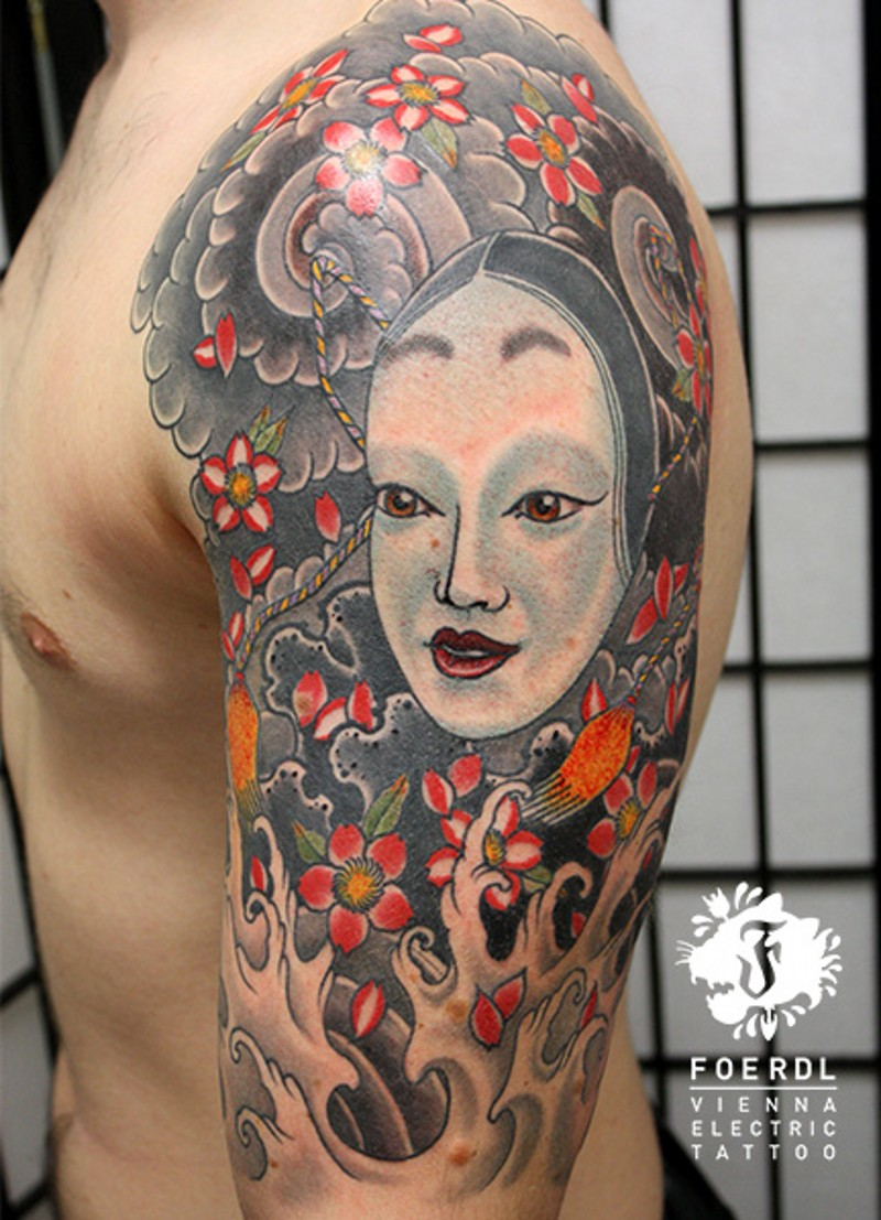 Cartoon style multicolored shoulder tattoo of Asian woman face with flowers