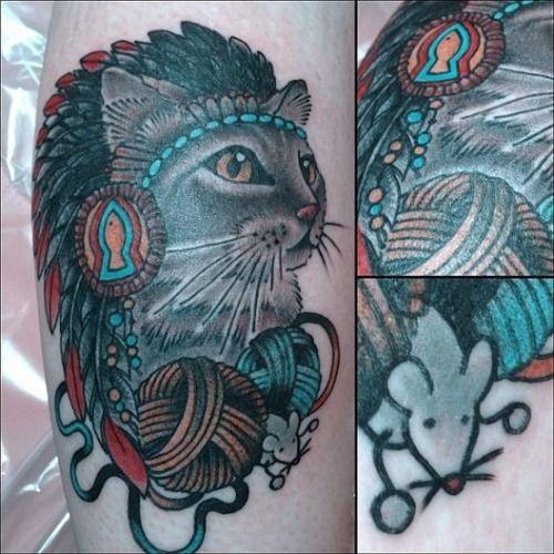 gatto in copricapo indiano con un gomitilo di lana e topo tatuaggio