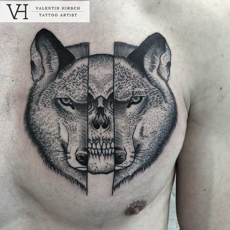 Chest tattoo designed by Valentin Hirsch of split wolf head with human skull