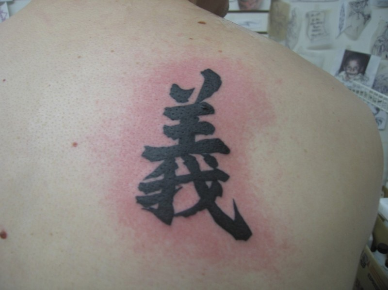 Chinese symbol tattoo on scapula