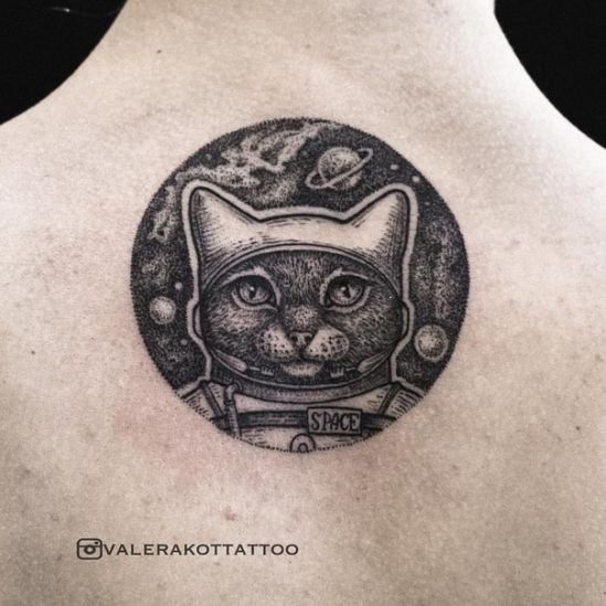 Circle shaped black ink back tattoo of cute cat astronaut