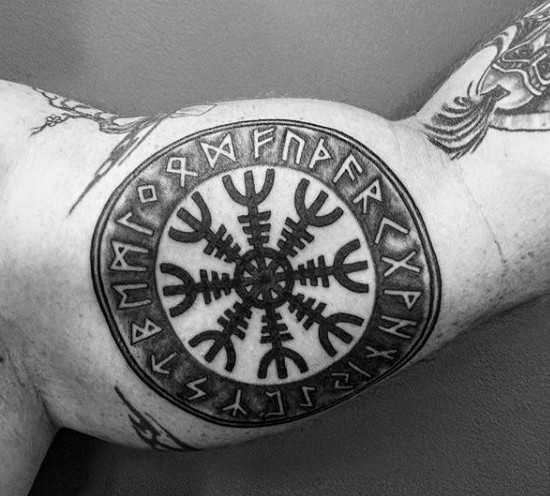 Circle shaped black ink biceps tattoo of ancient symbol with lettering