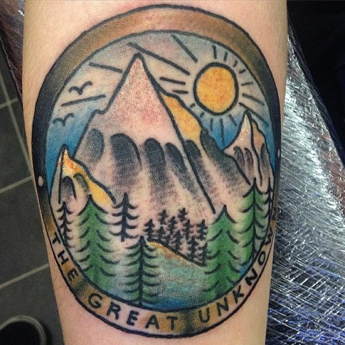 Circle shaped illustrative style colored leg tattoo of mountains view and lettering