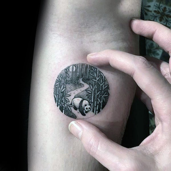 Circle shaped small tattoo stylized with night forest with panda bear