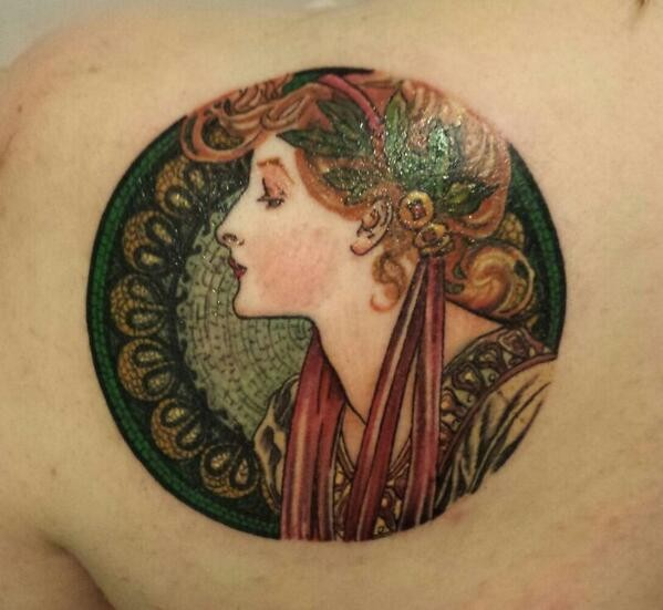Circle shaped vintage painting like colored shoulder tattoo of woman