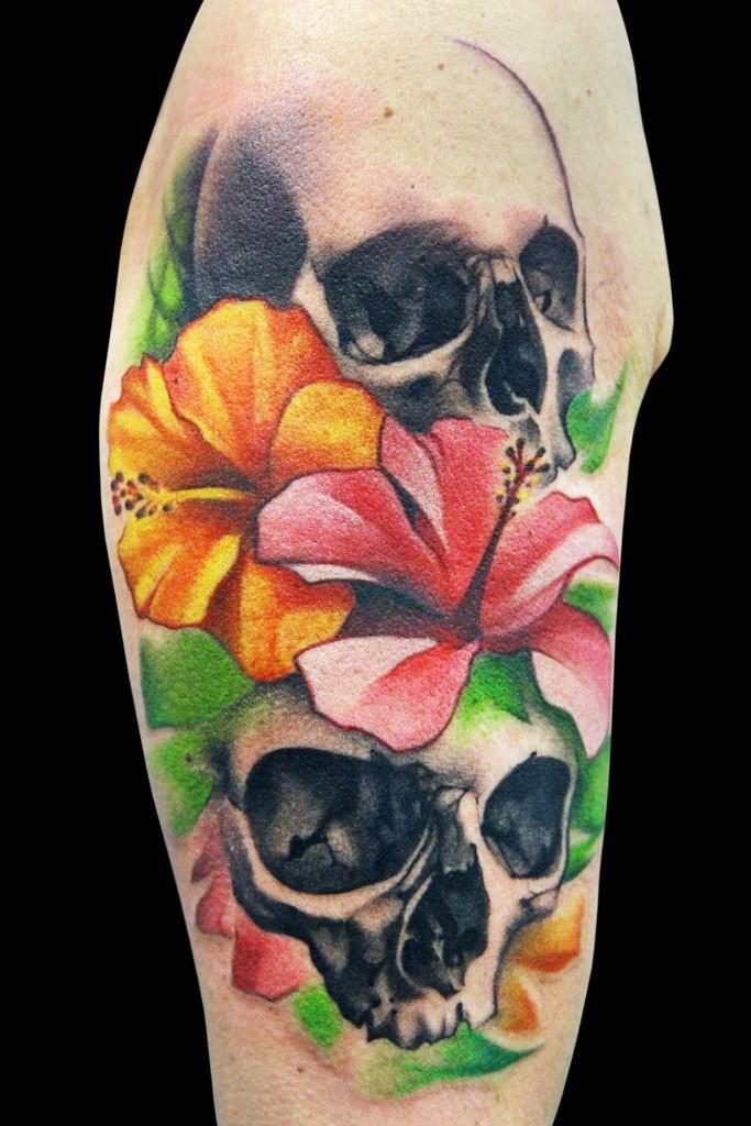 Tatuaggio sul deltoide i teschi con i fiori