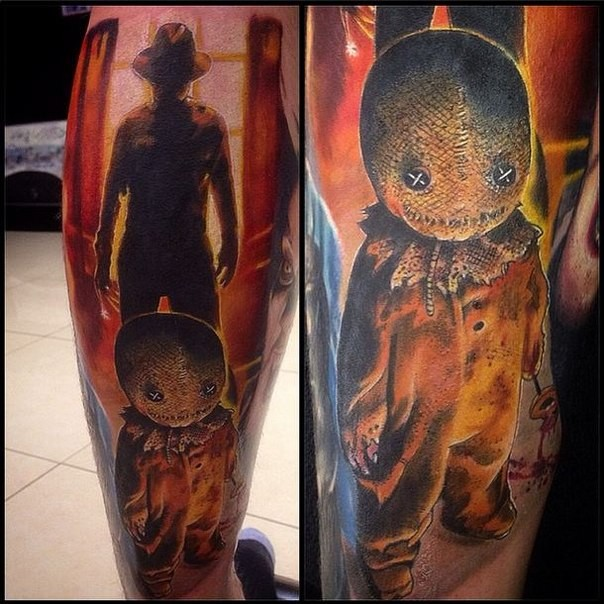 Colored creepy looking leg tattoo of evil doll with Freddy Kruger