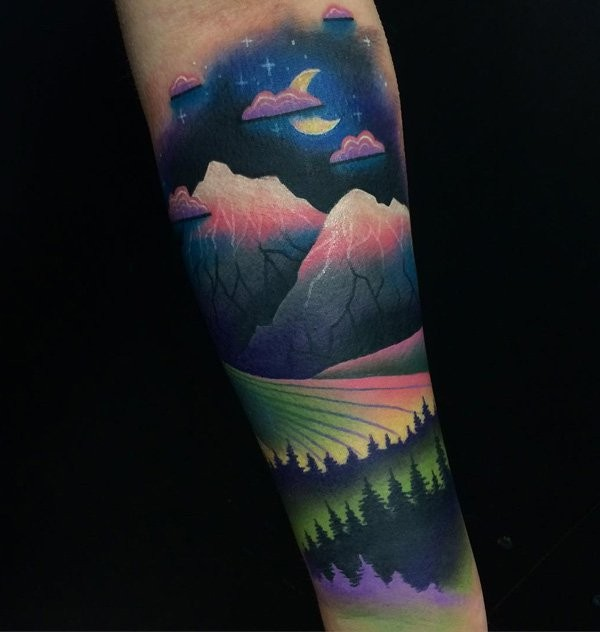 Colored forearm tattoo of night forest with mountains